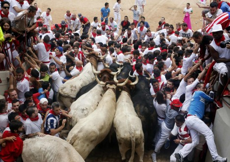 Runners get trapped with Fuente Ymbro fighting bulls during the seventh running of the bulls of the San Fermin festival in Pamplona -0MPG0180.jpg-