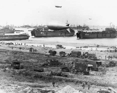 LSTs (Landing Ship Tanks), landing vehicles and cargo assemble on a Normandy beach in this June 1944 handout photo
