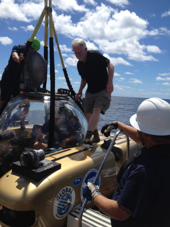 Mike Ruane, Washington Post staff writer, enters the manned submersible for a dive to the wreck sites. Image courtesy of Reed Bohne, Office of Marine National Sanctuaries