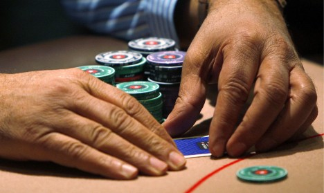 A contestant covers his cards during the Poker Stars tournament in London -SLP105_BRITAIN__1001_11.JPG-