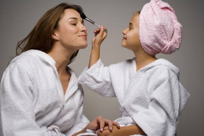 Girl (8-9) caressing mothers face with brush