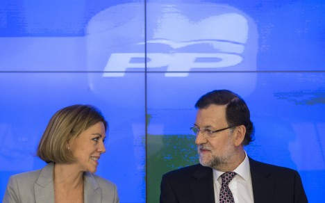 Spain's PM Rajoy listens to secretary general de Cospedal during their ruling People's Party (PP) National Executive Committee at the party's headquarters in Madrid
