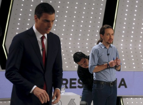 Podemos party leader Iglesias has his microphone adjusted by a technician as PSOE leader Sanchez stands before a live debate in San Sebastian de los Reyes