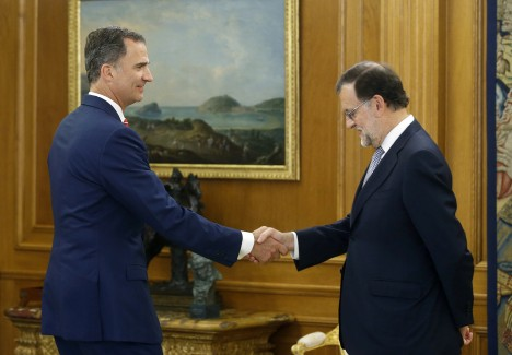 Spain's King Felipe greets acting PM Rajoy before their meeting at Zarzuela Palace in Madrid