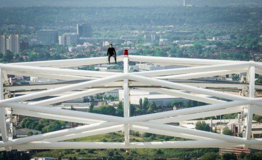 Un escalador trepa hasta la zona más alta del arco del estadio de Wembley