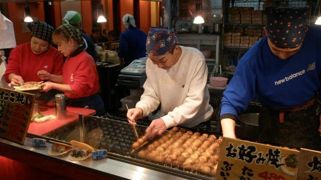 "Dotonbori saboreando su tradicional ""takoyaki"","