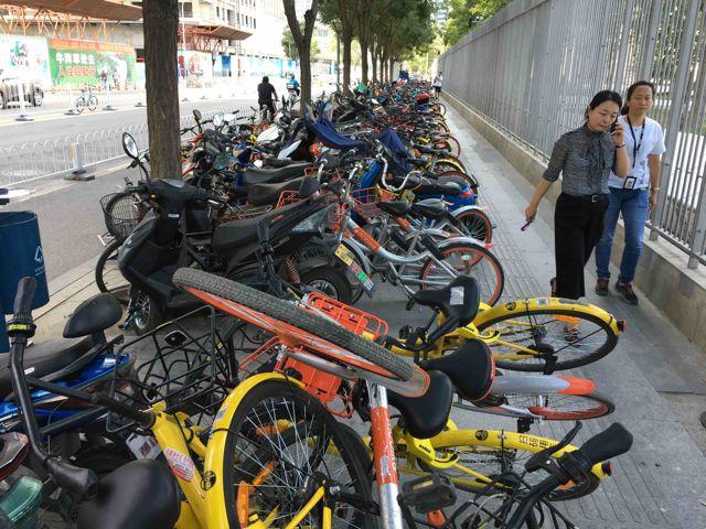 Amontanadas unas sobre otras, las bicicletas compartidas ocupan las aceras y apenas dejan espacio al peatón.