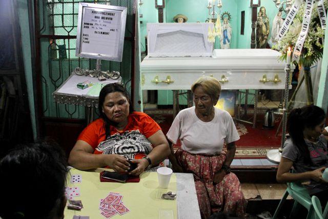 Velatorio en plena calle por una víctima de la guerra contra la droga, donde los asistentes montan timbas de cartas para ayudar a pagar el funeral.