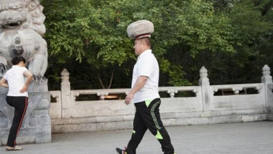 Un hombre camina con una piedra de 40 kilos en la cabeza para perder peso